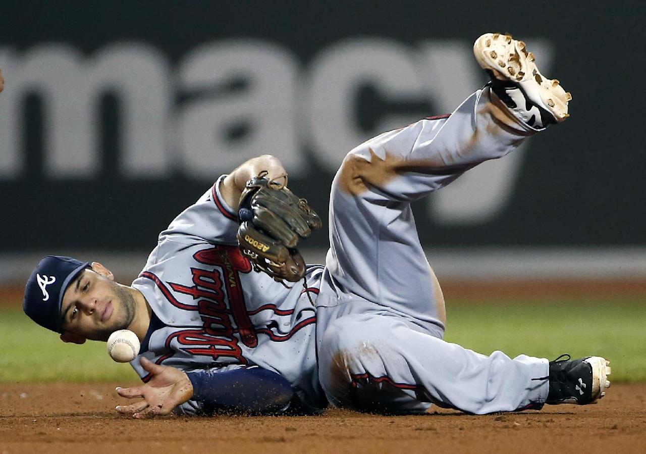 Atlanta Braves second baseman Tommy La Stella bobbles an infield hit by Boston Red Sox's Dustin Pedroia during the eighth inning of a baseball game at Fenway Park, Thursday, May 29, 2014, in Boston. (AP Photo/Winslow Townson)