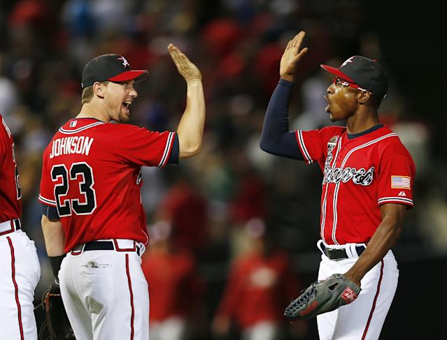 Atlanta Braves Chris Johnson, left, and B.J. Upton celebrate after defeating the Arizona Diamondbacks 5-2 in a baseball game in Atlanta, Friday, July 4, 2014. (AP Photo/John Bazemore)