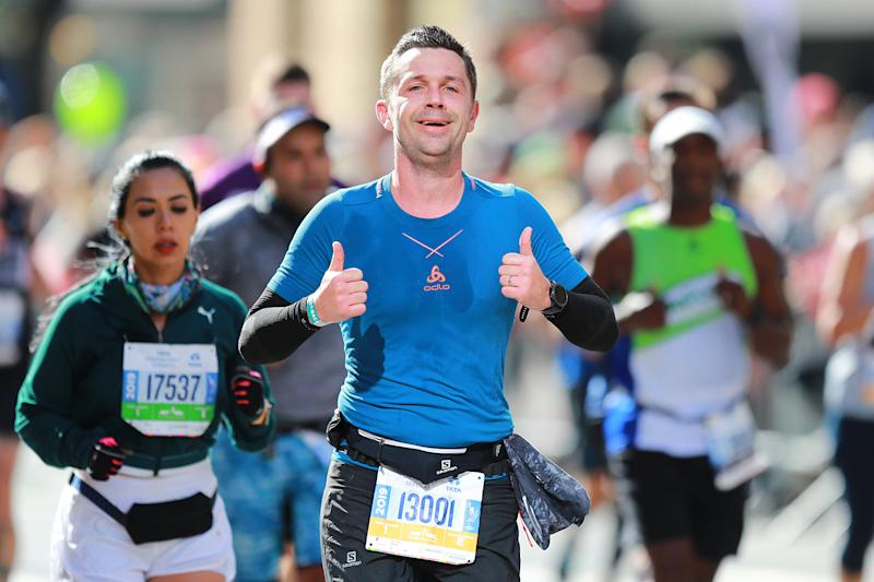 A participant gives two thumbs up while running in the 2019 New York City Marathon. (Photo: Gordon Donovan/Yahoo News)