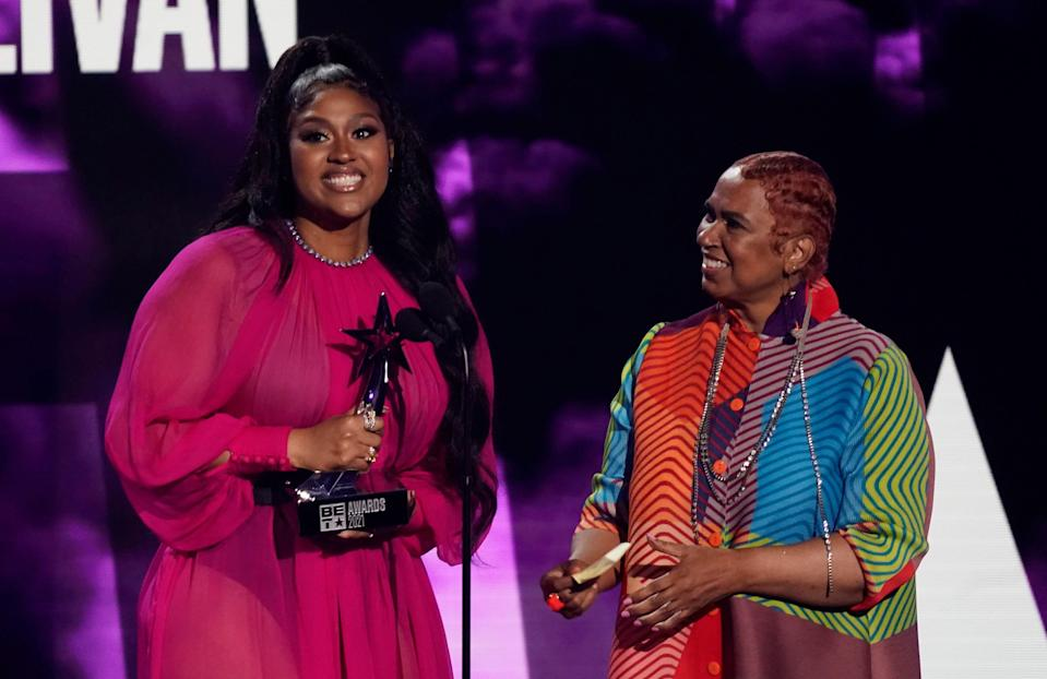 """Jazmine Sullivan accepts the album of the year award for """"Heaux Tales"""" as her mother Pam Sullivan looks on."""