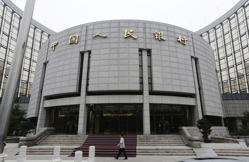 A staff member walks in front of the headquarters of the People's Bank of China, the central bank, in Beijing