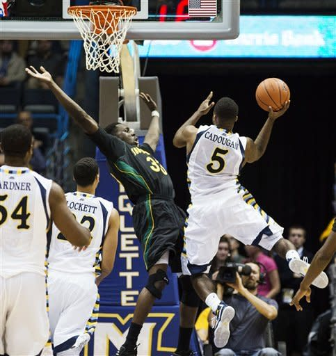 Marquette's Junior Cadougan (5) shoots over Southeastern Louisiana's Quin Cooper during the second half of an NCAA college basketball game, Tuesday, Nov. 13, 2012, in Milwaukee. (AP Photo/Tom Lynn)