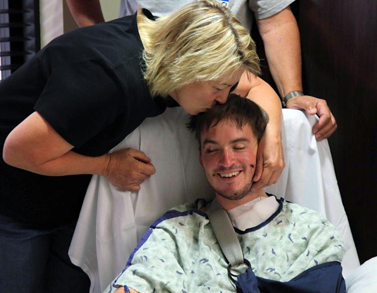 "Christine Barton kisses her son Stephen Barton, Sunday, July 22, 2012, at the Medical Center of Aurora, in Aurora, Colo. Stephen Barton, of Southbury, Conn., was wounded Friday when a gunman opened fire at a midnight showing of the new Batman movie, ""The Dark Knight Rises,"" in Aurora, where 12 people were killed and dozens more injured. (AP Photo/Robert Ray)"