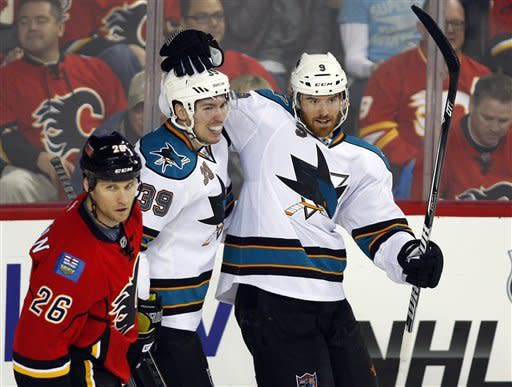 San Jose Sharks' Martin Havlat, right, of the Czech Republic, celebrates his goal with Logan Couture, left, as Calgary Flames' Dennis Wideman skates by during the second period of an NHL hockey game, Sunday, Jan. 20, 2013, in Calgary, Alberta. (AP Photo/The Canadian Press, Jeff McIntosh)