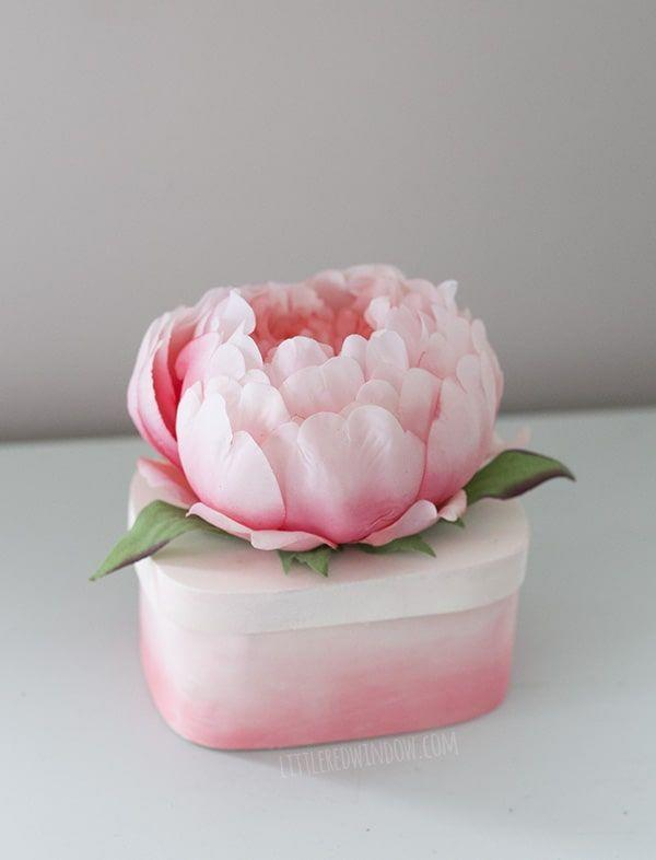 """<p>Not only is it the perfect accent to her vanity, but she can store all of her treasured jewels in this pretty in pink box. </p><p><a class=""""link rapid-noclick-resp"""" href=""""https://www.amazon.com/Luyue-Vintage-Artificial-Flowers-Decoration/dp/B01CVM5YKU?tag=syn-yahoo-20&ascsubtag=%5Bartid%7C10055.g.2412%5Bsrc%7Cyahoo-us"""" rel=""""nofollow noopener"""" target=""""_blank"""" data-ylk=""""slk:SHOP SILK PEONIES"""">SHOP SILK PEONIES</a></p><p><em><a href=""""https://littleredwindow.com/diy-flower-top-trinket-box/"""" rel=""""nofollow noopener"""" target=""""_blank"""" data-ylk=""""slk:Get the tutorial at Little Red Window »"""" class=""""link rapid-noclick-resp"""">Get the tutorial at Little Red Window »</a></em> </p>"""