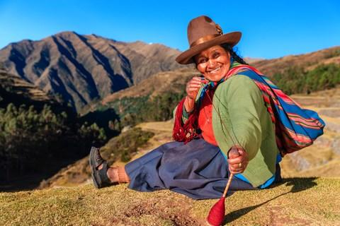 A Peruvian woman spinning wool by hand in the Sacred Valley - Credit: Getty