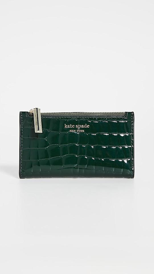 "<p>The deep evergreen color and croc print of this <a href=""https://www.popsugar.com/buy/Kate-Spade-New-York-Sylvia-Croc-Embossed-Small-Slim-Bifold-Wallet-522051?p_name=Kate%20Spade%20New%20York%20Sylvia%20Croc%20Embossed%20Small%20Slim%20Bifold%20Wallet&retailer=shopbop.com&pid=522051&price=128&evar1=fab%3Aus&evar9=44306518&evar98=https%3A%2F%2Fwww.popsugar.com%2Fphoto-gallery%2F44306518%2Fimage%2F46933516%2FKate-Spade-New-York-Sylvia-Croc-Embossed-Small-Slim-Bifold-Wallet&list1=shopping%2Cwallets%2Cgift%20guide%2Cfashion%20gifts%2Cgifts%20for%20women%2Cbest%20of%202018&prop13=api&pdata=1"" rel=""nofollow"" data-shoppable-link=""1"" target=""_blank"" class=""ga-track"" data-ga-category=""Related"" data-ga-label=""https://www.shopbop.com/sylvia-croc-embossed-small-slim/vp/v=1/1502525402.htm?folderID=13514&amp;fm=other-viewall&amp;os=false&amp;colorId=148AC"" data-ga-action=""In-Line Links"">Kate Spade New York Sylvia Croc Embossed Small Slim Bifold Wallet</a> ($128) make it one-of-a-kind. </p>"