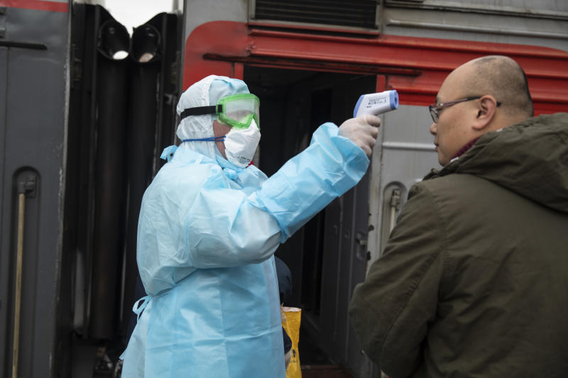 A medical worker in a hazardous materials suit uses a body thermal scanner to check temperature of Chinese passenger who just arrived from Beijing at the Yaroslavsky railway station in Moscow, Russia, Friday, Jan. 31, 2020. Russia has reported the first two cases of a new virus in the country. (AP Photo/Pavel Golovkin)