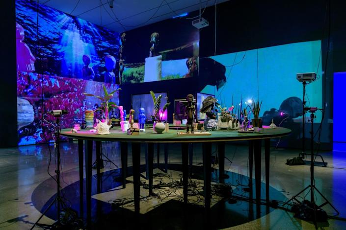 Statues, dolls and plants sit on a table under images projected on several surrounding walls.