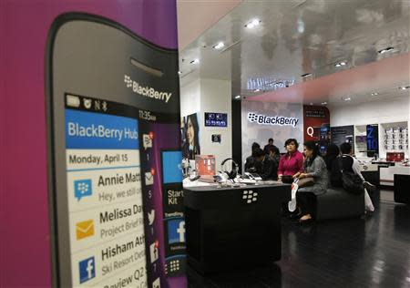 Customers waiting for repair services look on at a BlackBerry service centre in Jakarta