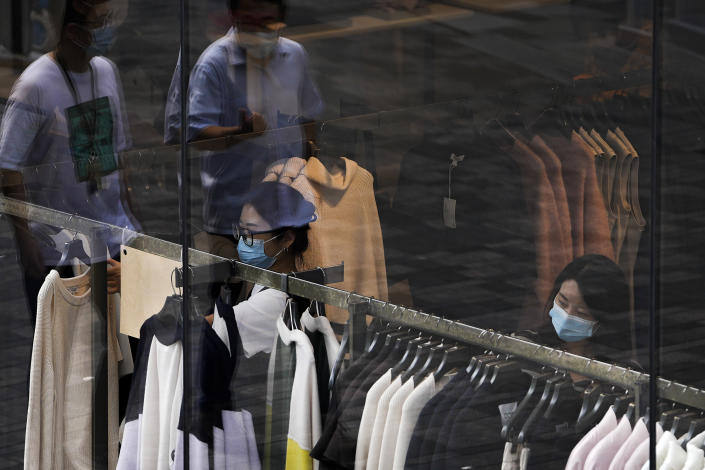 People wearing face masks to help protect from the coronavirus walk through a capital popular shopping mall as masked women selecting clothes at a fashion boutique in Beijing, Tuesday, Sept. 28, 2021. The World Bank on Tuesday cut its economic growth forecast for developing countries in East Asia due to the impact of the coronavirus's delta variant and called on governments to help the poor and small businesses avoid long-term damage. (AP Photo/Andy Wong)