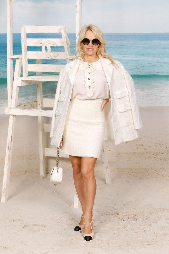 <p>Pamela Anderson arrived at the Grand Palais on October 2 in a white co-ord by Chanel. She accessorised the super chic look with sunnies and shoes by the French fashion house. <em>[Photo: Getty]</em> </p>