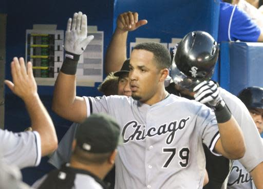 Chicago White Sox's Jose Abreu is congratulated in the dugout after he hit his second home run of the night off Toronto Blue Jays starting pitcher R.A. Dickey during the seventh inning of their baseball game in Toronto on Friday, June 27, 2014. (AP Photo/The Canadian Press, Fred Thornhill)