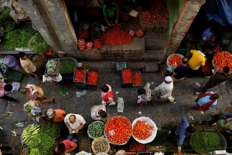 People shop at a crowded wholesale vegetable market after authorities eased coronavirus restrictions, following a drop in COVID-19 cases, in the old quarters of Delhi