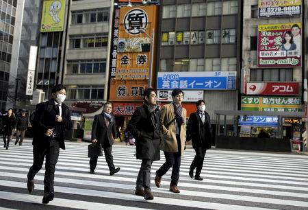 FILE PHOTO: People cross a street in a business district in Tokyo, Japan,  February 16, 2016. REUTERS/Thomas Peter