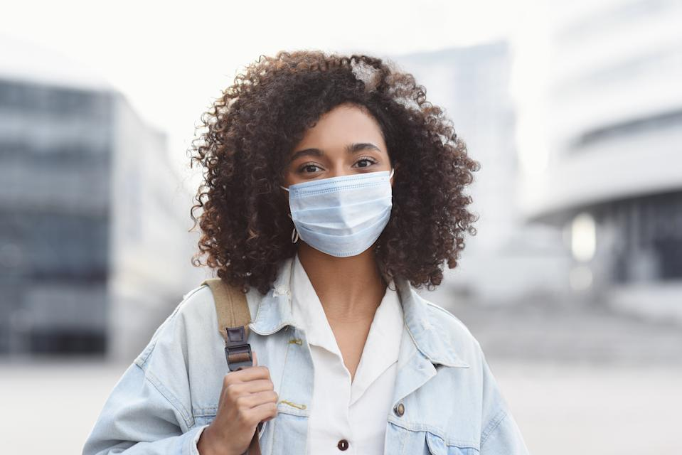 Masked african-american woman on a city street. Teenage girl patient, copy space. Epidemic, pandemic, corona virus protection, healthy lifestyle, people concept