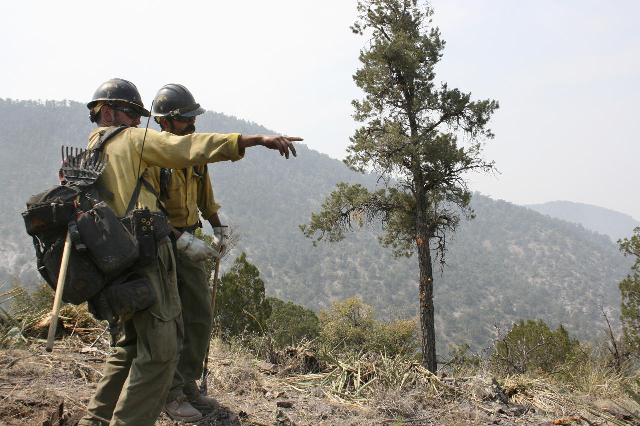 Crew members from the Granite Mountain Hotshots of Prescott, Ariz., cut a fire line along a mountain ridge outside Mogollon, N.M., Saturday, June 2, 2012, in an effort to manage and contain the Whitewater-Baldy fire which has burned more than 354 square miles of the Gila National Forest in New Mexico. Unlike last year's megafires in New Mexico and Arizona, this blaze is burning in territory that has been frequently blackened under the watchful eye of the Gila's fire managers. (AP Photo/U.S. Forest Service, Tara Ross)