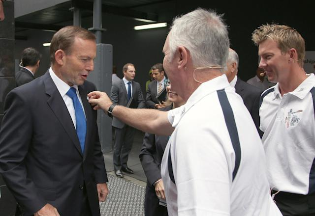 Former Australian cricket captain Allan Border, center, touches a badge on the jacket lapel of Australian Prime Minister Tony Abbott, left, as they arrive for a ceremony in Sydney, Friday, Feb. 14, 2014, marking one year to the start of the 2015 ICC World Cup Cricket tournament. Organizers are expecting more than one million people to attend the 49 matches in Australia and New Zealand starting on Feb. 14, 2015. (AP Photo/Rick Rycroft)