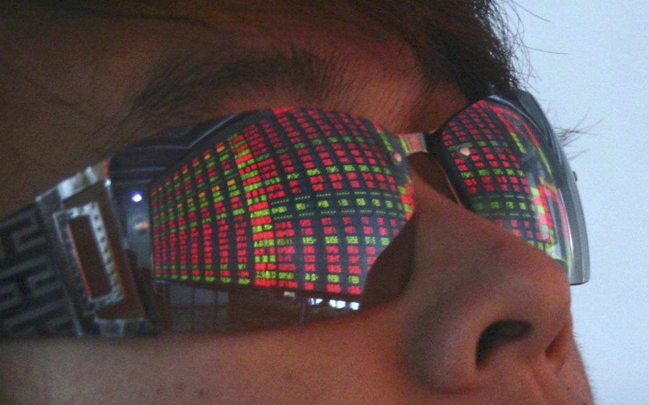 File picture of a college student watching an electronic stock board at a stock exchange in Xiamen