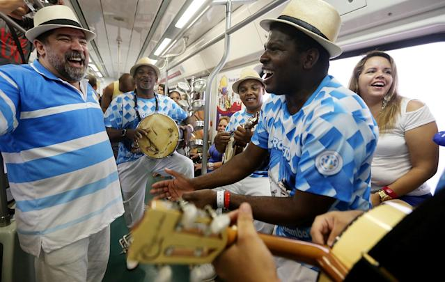 RIO DE JANEIRO, BRAZIL - DECEMBER 07: Revelers perform on the 'Samba Train' on December 7, 2013 in Rio de Janeiro, Brazil. The 'Samba Train' takes samba lovers once per year via a commuter train to the neighborhood of Oswaldo Cruz to dance while marking the National Day of Samba. Samba is considered Brazil's national rhythm and can be traced to Brazil's slave trade from West Africa. (Photo by Mario Tama/Getty Images)