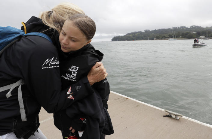 Climate change activist Greta Thunberg gets a hug before she boards the Malizia II boat in Plymouth, England, Wednesday, Aug. 14, 2019. The 16-year-old climate change activist who has inspired student protests around the world will leave Plymouth, England, bound for New York in a high-tech but low-comfort sailboat.(AP Photo/Kirsty Wigglesworth, pool)