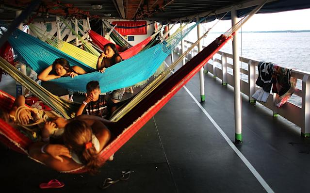 MANAUS, BRAZIL - NOVEMBER 24: Passengers sit in their hammocks while departing on a transport riverboat in the Brazilian Amazon from Manaus to Maues on November 24, 2013 in Manaus, Brazil. The approximately 20-hour journey in the riverboat costs about $25 USD and includes three meals while most passengers sleep in their own hammocks, usual for Amazon riverboat travel. Riverboats ferry people and cargo throughout the Amazon and often serve as the primary form of mass transportation. Manaus' Arena Amazonia will be a stadium venue during the forthcoming FIFA 2014 World Cup Brazil. Manaus is the largest city in the Amazon holding around 2 million and is the main hub for transport in the Upper Amazon basin. (Photo by Mario Tama/Getty Images)