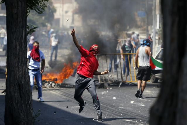 A Palestinian throws a stone during clashes with Israeli police after prayers on the first Friday of the holy month of Ramadan in the East Jerusalem neighbourhood of Wadi al-Joz July 4, 2014. Palestinians infuriated at the kidnap and killing of 16-year-old Mohammed Abu Khudair, which they blame on far-right Jews, clashed with Israeli police in Jerusalem on Friday, while cross-border shelling in the Gaza Strip abated under Egyptian mediation. Ahead of Abu Khudair's funeral, Israeli police deployed extra forces in Jerusalem and barred men under the age of 50 from al Aqsa mosque complex, the city's most sacred Muslim site, forcing hundreds of men to hold prayers outside the gates of the Old City. REUTERS/Baz Ratner (JERUSALEM - Tags: POLITICS CIVIL UNREST RELIGION)