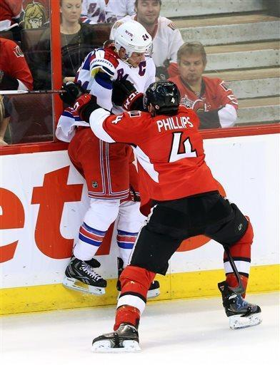 Ottawa Senators' Chris Phillips (4) checks New York Rangers' Ryan Callahan into the boards during the first period of their NHL hockey game, Thursday, March 28, 2013, in Ottawa, Ontario. (AP Photo/The Canadian Press, Fred Chartrand)