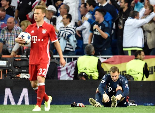 Bayern Munich goalkeeper Manuel Neuer (R) removes his boot during the Champions League quarter-final second leg against Real Madrid at the Santiago Bernabeu stadium in Madrid on April 18, 2017 (AFP Photo/Gerard JULIEN)