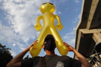 A protester holds a balloon shaped like an alien - to mock accusations that foreigners fund and direct their movement - during a rally Friday, Nov. 27, 2020 in Bangkok, Thailand. Pro-democracy demonstrators are continuing their protests calling for the government to step down and reforms to the constitution and the monarchy, despite legal charges being filed against them and the possibility of violence from their opponents or a military crackdown. (AP Photo/Sakchai Lalit)