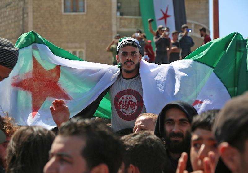 Syrian protesters wave the flag of the opposition as they demonstrate against the regime and its ally Russia, in the rebel-held city of Idlib on September 7, 2018 (AFP Photo/Zein Al RIFAI)