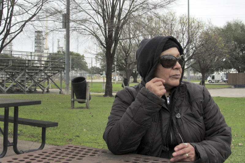 In this Thursday, Jan. 30, 2020, photo, Houston resident Guadalupe Ortiz sits at a city park located across the street from her home and a Valero oil refinery. Houston's lack of zoning has resulted in residents like Ortiz living next to petrochemical facilities and businesses that handle hazardous substances.  (AP Photo/ Juan Lozano)
