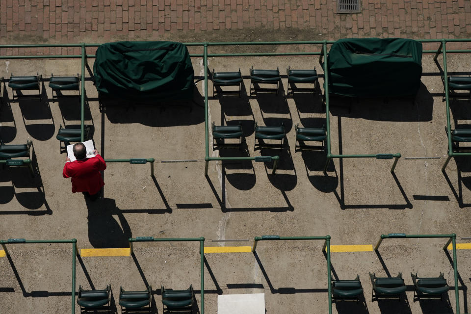 A man looks over a racing program before the 147th running of the Kentucky Derby at Churchill Downs, Saturday, May 1, 2021, in Louisville, Ky. (AP Photo/Charlie Riedel)