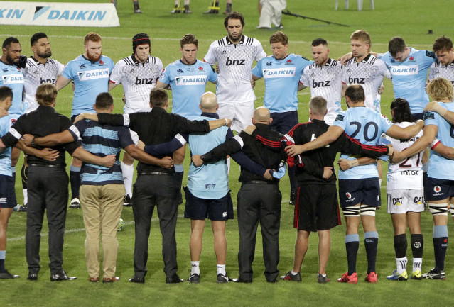 The Waratahs and the Crusaders Super Rugby teams join together, including Waratahs' captain Michael Hooper, center left, and Crusaders' captain Sam Whitelock, center right, stand together for a moment of silence for the New Zealand shooting victims before their Super Rugby game in Sydney, Australia, Saturday, March 23, 2019. (AP Photo/Rick Rycroft)