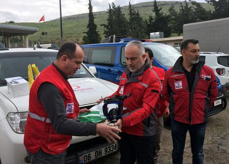 Kerem Kinik, head of the Turkish Red Crescent, holds a gas mask as he talks to his team members at the Cilvegozu border gate which is located opposite of Syrian commercial crossing point Bab al-Hawa, in Hatay province