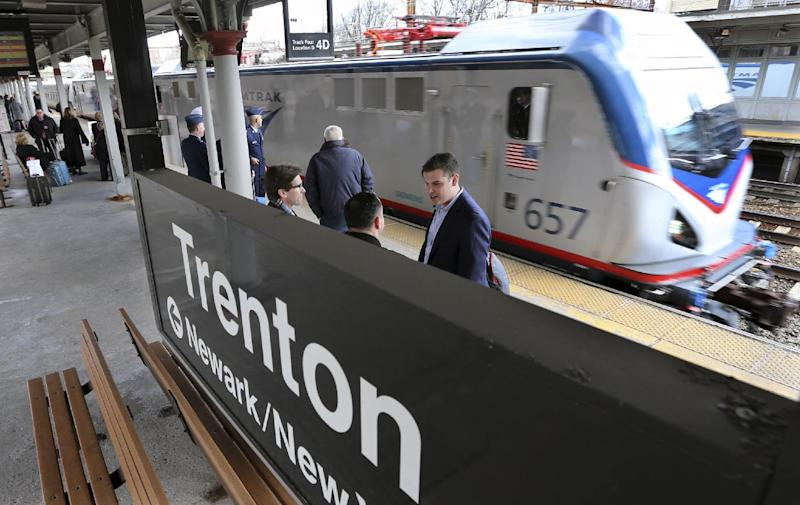 """Some of the 1,000 lobbyists, business owners and politicians gather on a platform at the Trenton train station as a train arrives to take them to Washington, D.C., Thursday, Feb. 16, 2017 in Trenton, N.J. The state Chamber of Commerce's 80th annual trip — nicknamed the """"Walk to Washington"""" because rail riders generally pace the train's corridors schmoozing and handing out business cards — comes after a national election that hinged in part on repudiating insiders and establishment politics. (AP Photo/Mel Evans)"""