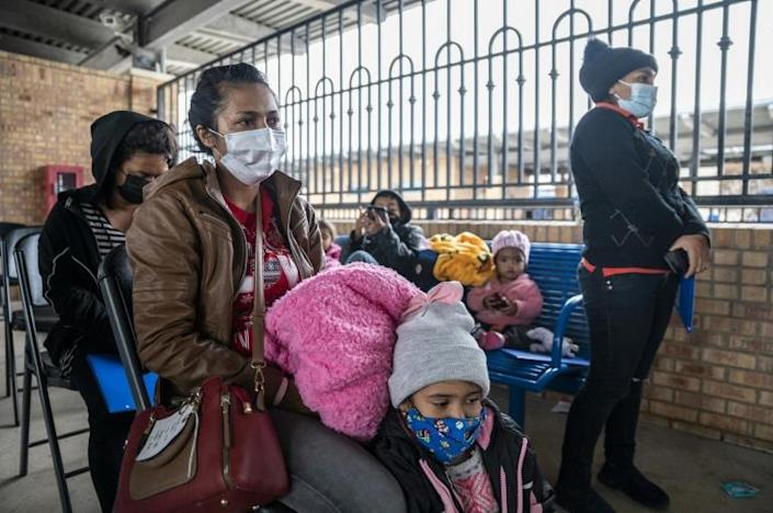 Migrant families wait for their bus in Brownsville, Texas before travelling to meet relatives or sponsors after being allowed to remain in the United States despite their lack of immigration papers.