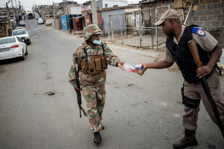 A South African soldier (left) hands over cigarettes he seized from a small shop to a policeman. The tobacco ban is still in force