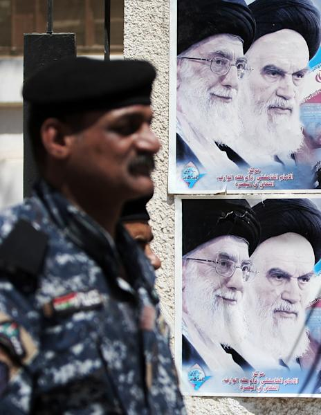 FILE - In this file photo taken on Sept. 12, 2012, photo, an Iraqi soldier stands guard next to a poster depicting late Iran's spiritual leaders Ayatollah Khomeini, right, and Ayatollah Khamenei, left, in Basra, 340 miles (547 kilometers) southeast of Baghdad, Iraq, Iraqi officials and militant groups say Iranian-backed Shiite militias are threatening to retaliate against American interests inside Iraq if the United States goes ahead with strikes against Syrian President Bashar Assad's regime, a close ally of Tehran. Such attacks risk exacerbating the deteriorating security environment inside Iraq. (AP Photo/Nabil al-Jurani, File)
