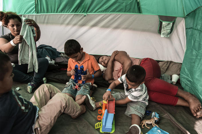 Mirna is resting while Xinia, left, is sorting new clothes and, from right, Kevin, Schneider and Oliver are playing with games donated by volunteers at El Barretal shelter in Tijuana, Mexico, on Dec. 2, 2018. (Photo: Fabio Bucciarelli for Yahoo News)