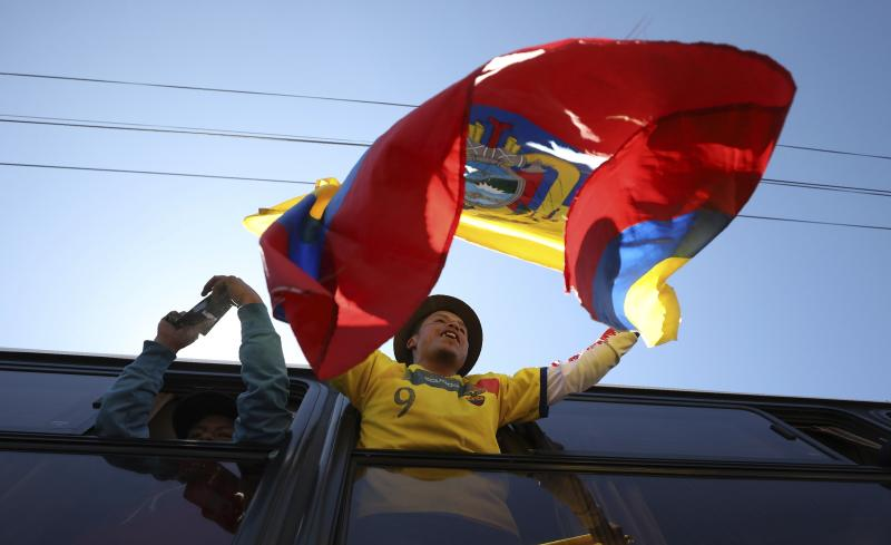 An anti-austerity protester waves a national flag as he rides away in a bus to return home, in the aftermath of violent protests against the government, in Quito, Ecuador, Monday, Oct. 14, 2019. Ecuador celebrated a deal President Lenín Morenoand indigenous leaders struck late Sunday to cancel a disputed austerity package and end nearly two weeks of protests that have paralyzed the economy and left seven dead.(AP Photo/Fernando Vergara)