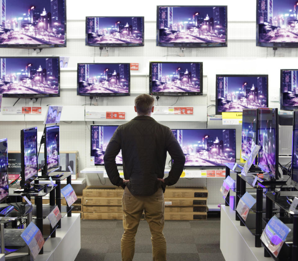 Man stood in shop surrounded by televisions