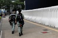 Riot police officers walk past a barricade outside Legislative Council Complex as a second reading of a controversial national anthem law takes place in Hong Kong