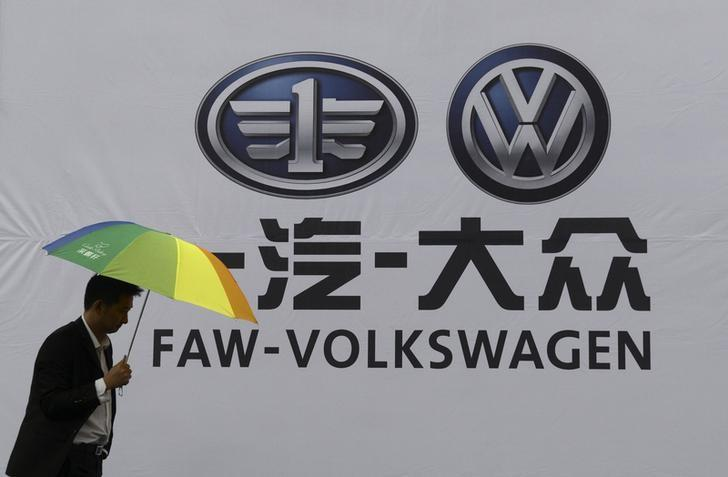 A man holds an umbrella as he walks past a company logo of FAW-Volkswagen at an automobile exhibition in Fuyang