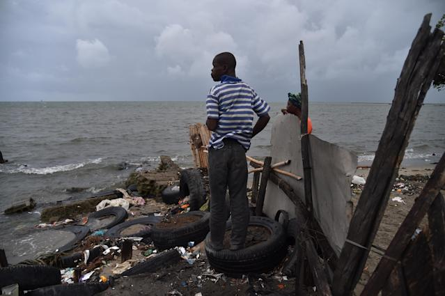<p>Jean looks at the sea from a house where he is working in the neighborhood of Aviation in Cap-Haitien, Haiti, on Sept. 7, 2017. (Photo: Hector Retamal/AFP/Getty Images) </p>
