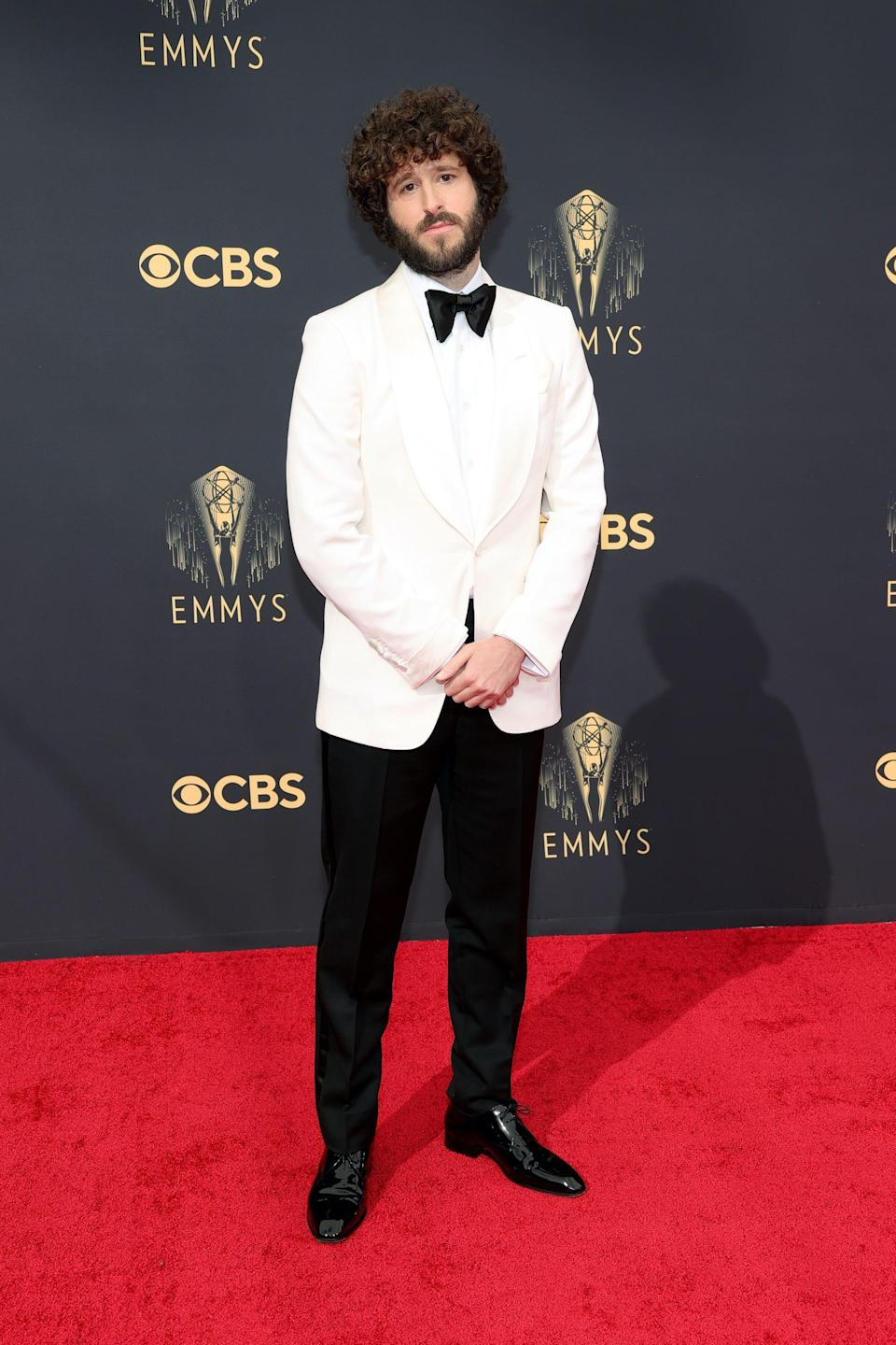 Dave Burd wears a white tuxedo jacket and black pants on the Emmys red carpet.