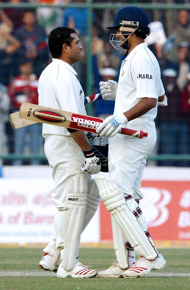 Former Indian cricket captain Sourav Ganguly (R) congratulates India's star batsman Sachin Tendulkar after Tendulkar reached his century during the first day of the second test match between India and Sri Lanka in New Delhi, 10 December 2005. Sachin Tendulkar scored a record 35th Test century to help India reach 245-3 against Sri Lanka on the opening day of the second Test.   AFP PHOTO/RAVEENDRAN