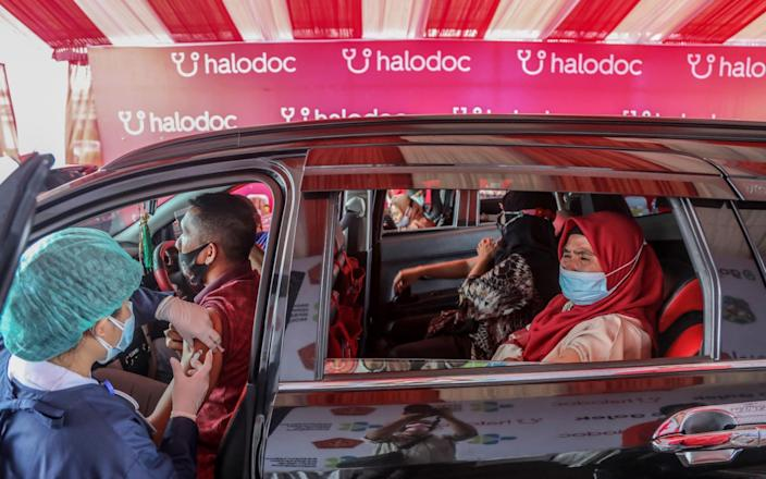 Healthcare workers inject doses of Sinovac Covid-19 vaccine during a drive-through vaccination drive in Medan, North Sumatra, Indonesia - Dedi Sinuhaji/Shutterstock