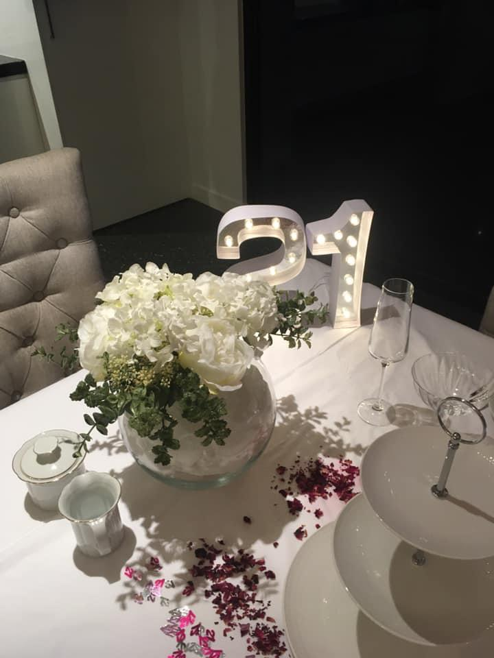 A table decorated with a light-up number 21 and faux flowers in vases
