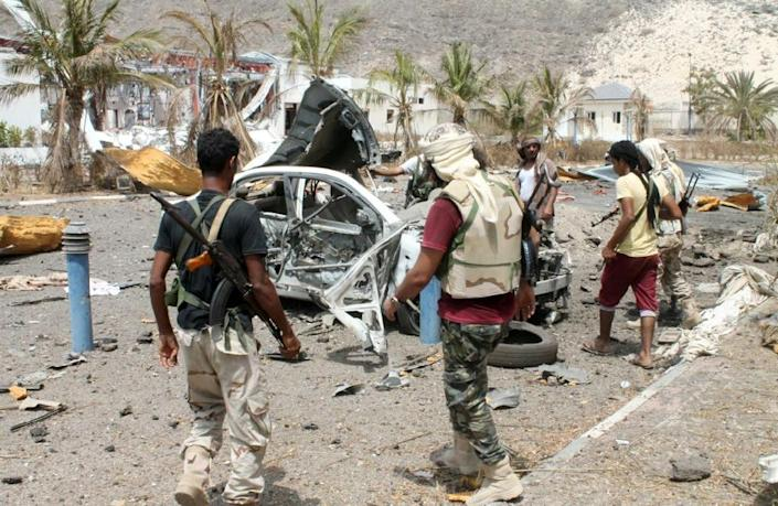 Fighters loyal to Yemen's exiled President Abedrabbo Mansour Hadi stand next to a destroyed vehicle in Aden on July 20, 2015 (AFP Photo/Saleh al-Obeidi)